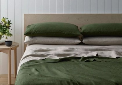 A green and beige bedding set on a double bed with a stack of pillows.