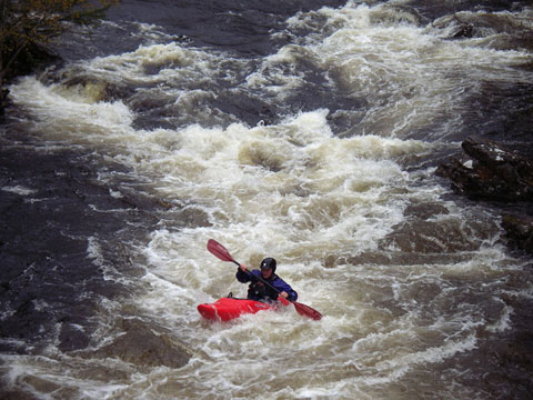 White water kayaking: A kayaker on a white water rapid.
