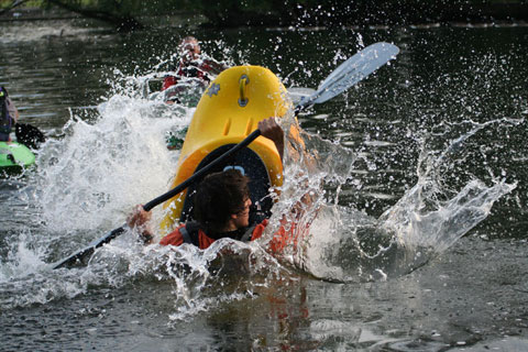 Freestyle kayaking. This freestyle kayaker uses his body and paddle to rotate his kayak into a vertical position on the water. Freestyle is also known as playboating.