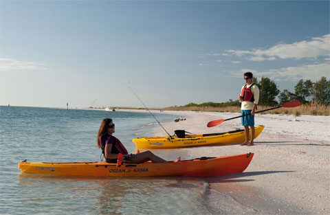 Two paddlers with sit on top kayaks, on a beach