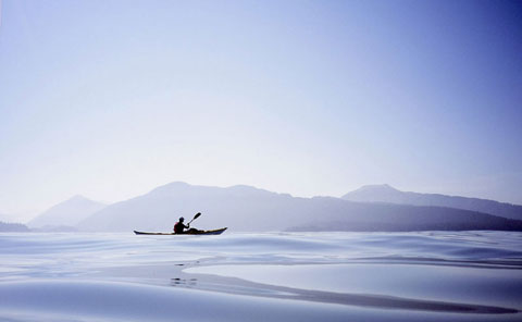 Sea kayaking: A kayaker paddles over a beautiful blue sea in a sea kayak.