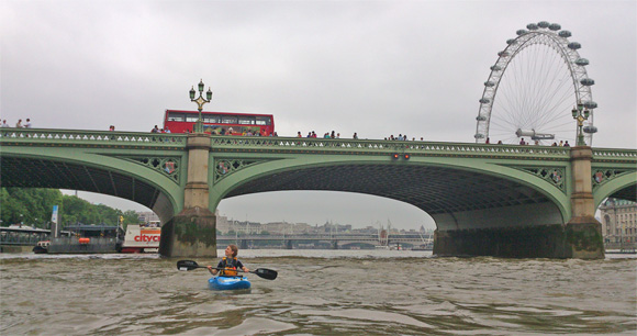 A kayaker on the River Thames, with bridge and the London Eye behind them