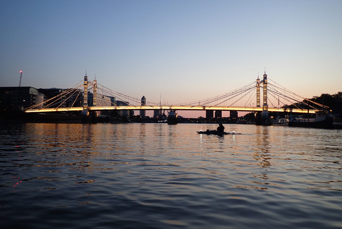 The illuminated Albert Bridge as dusk falls from a clear sky. A single kayaker is silhouetted on the water