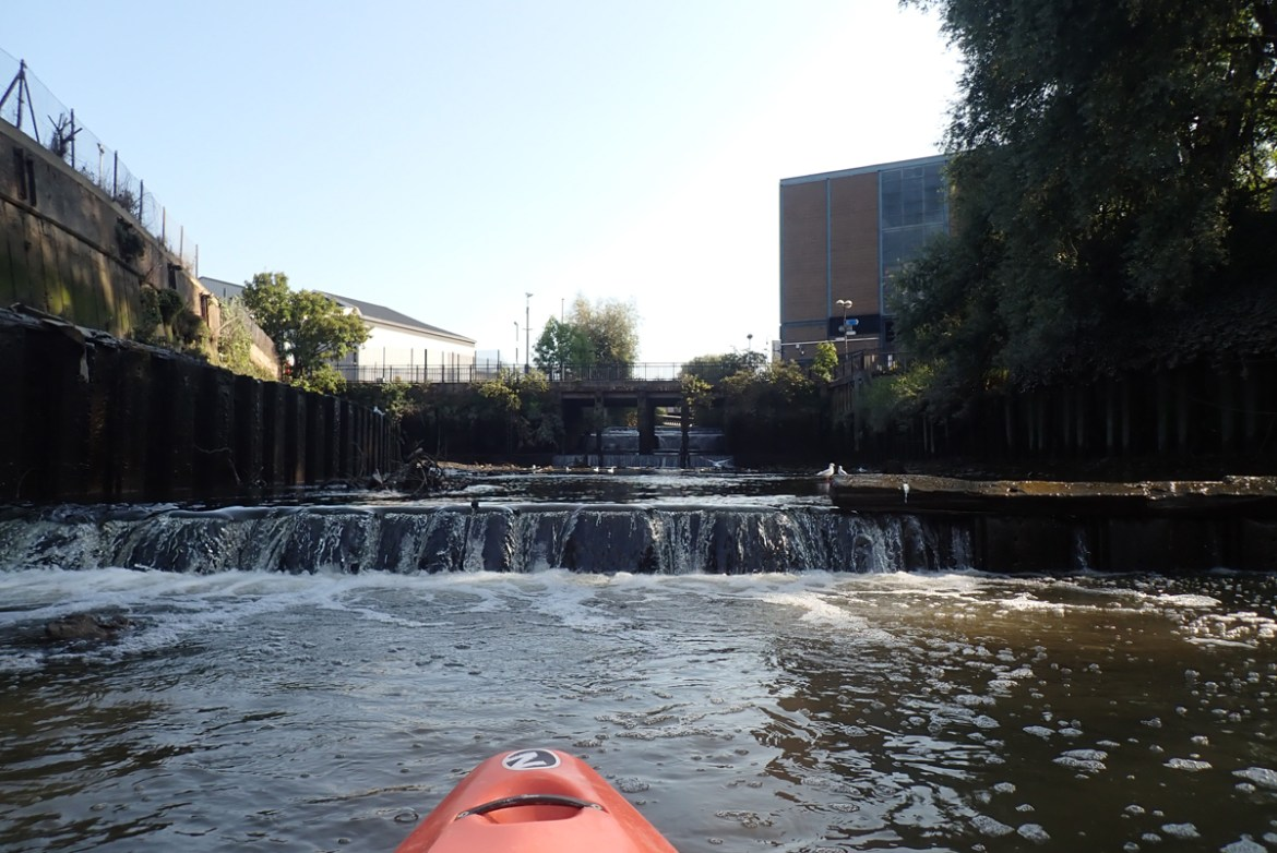 Looking upstream to water flowing over low weirs on the River Wandle