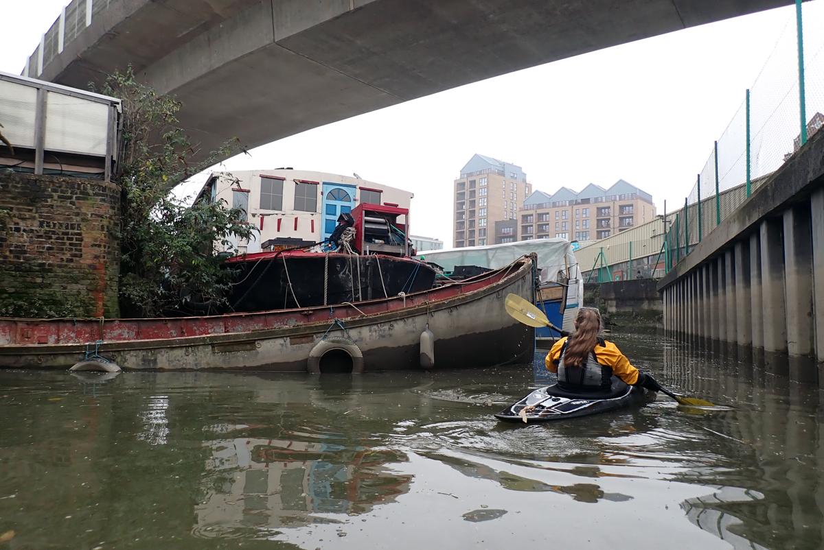 Kayaker below a concrete railway bridge, next to a sunken boat