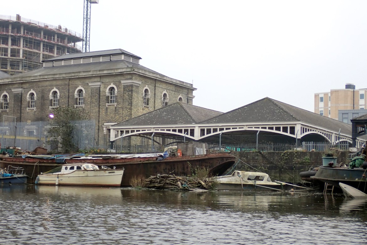Ornate Victorian architecture next to Deptford Creek, with abandoned boats in the foreground.