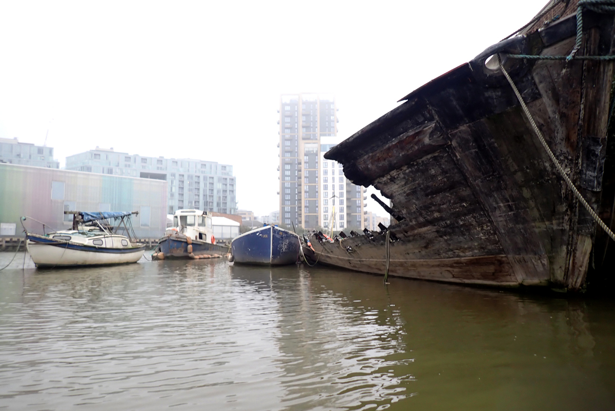 Deptford Creek. A large wooden boat tilts to one side. Most of the visible side has been burnt or cut away. There is no deck. Next to the burnt boat, several smaller boats float in the water. Modern buildings rise in the background.