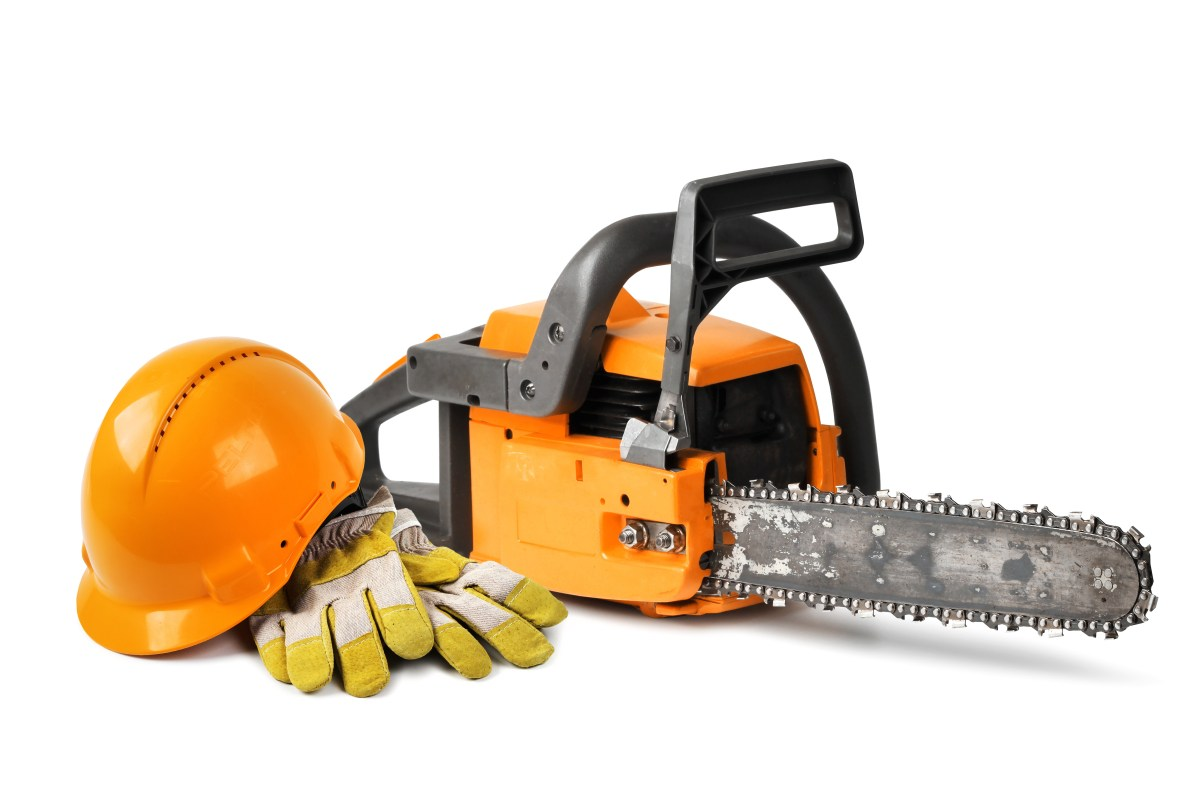 Chain saw and orange hard hat isolated, safety concept