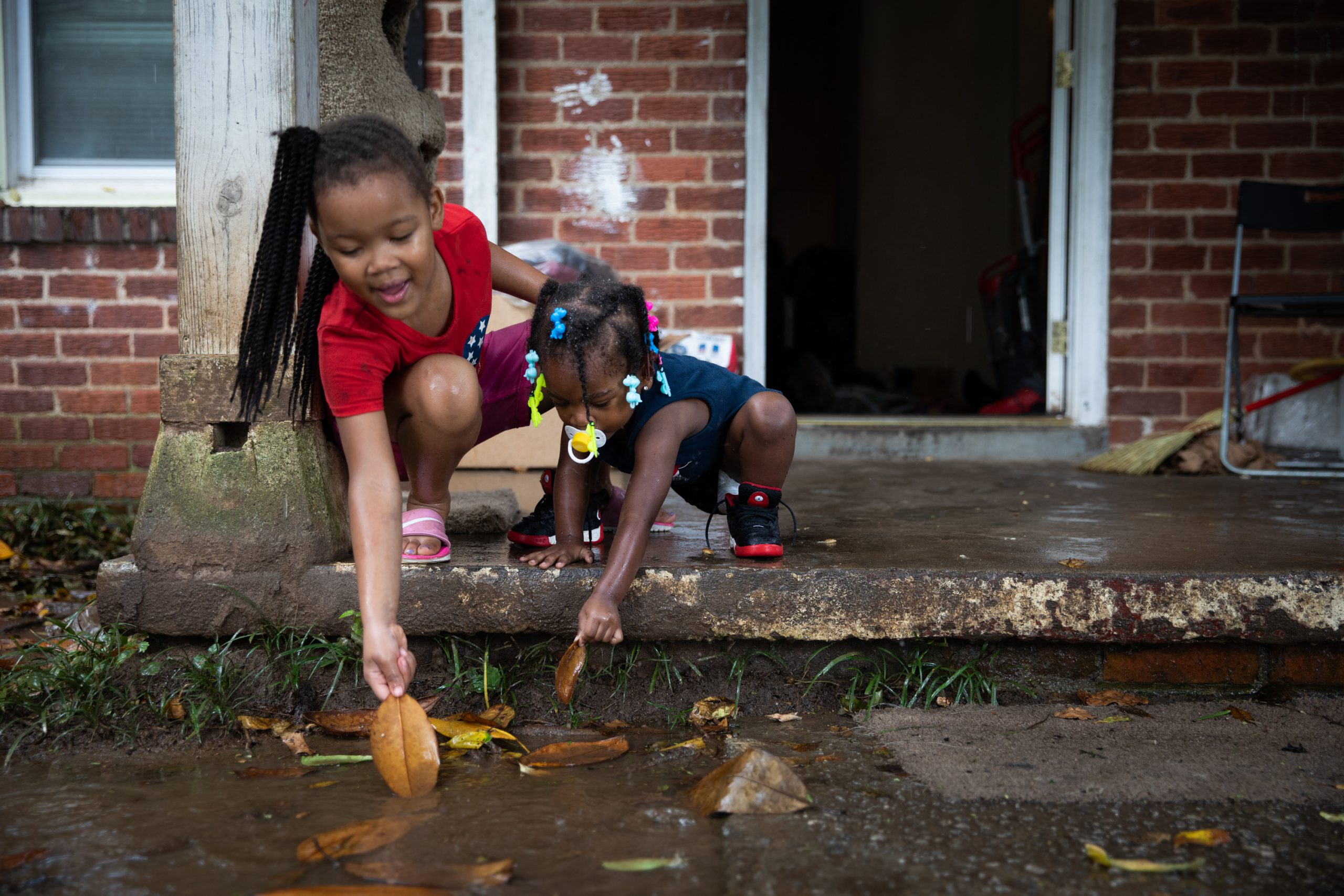 Two young girls play with leaves in rain outside