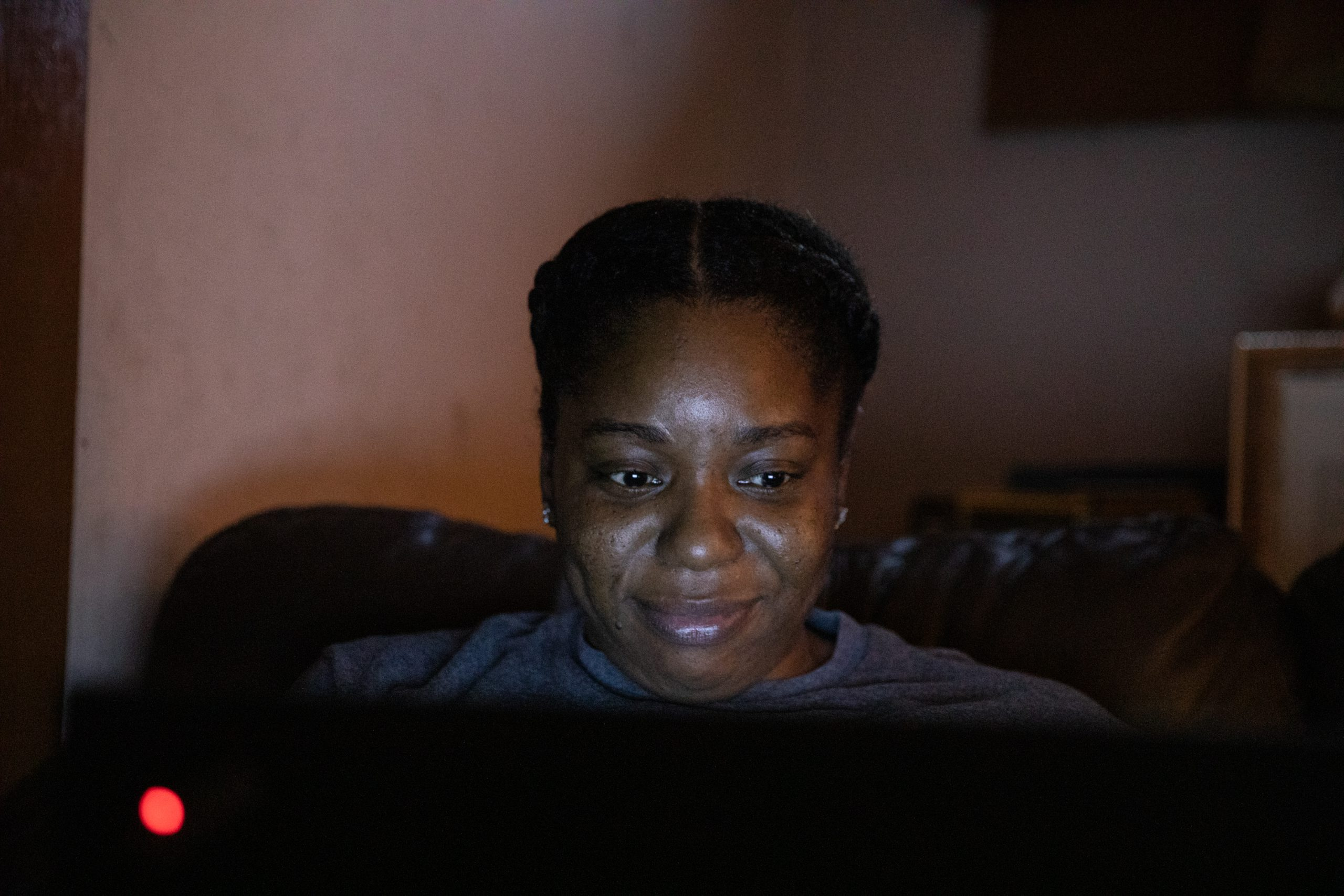 A woman smiles at her laptop