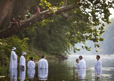 Seven people being baptized in the Jordan River