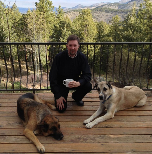 Father Brendan Rolling, O.S.B with two dogs.