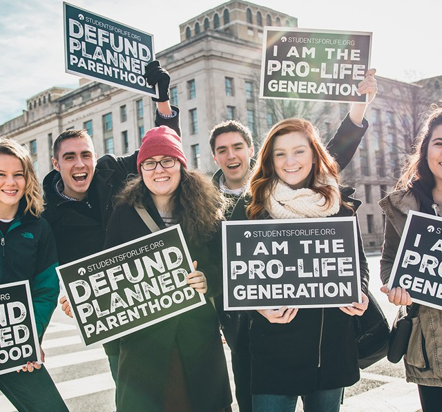 Students for life rally in 2018 (two boys and four girls, the second to the right is Autumn Lindsey, student spokesperson) holding pro-life signs.