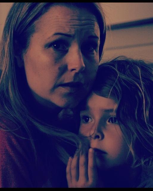 Mãe e filhas abraças com medo.