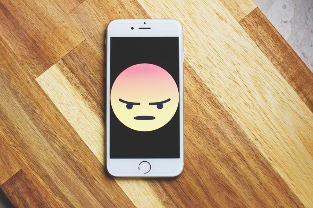White iPhone with an angry emoji face in a black background on a wooden table