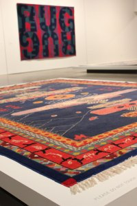 "An untitled work by Italian conceptual artist Alighiero e Boetti greets viewers to ""Wall to Wall."" In the background is ""Carpet Rug"" by Heimo Zobernig."
