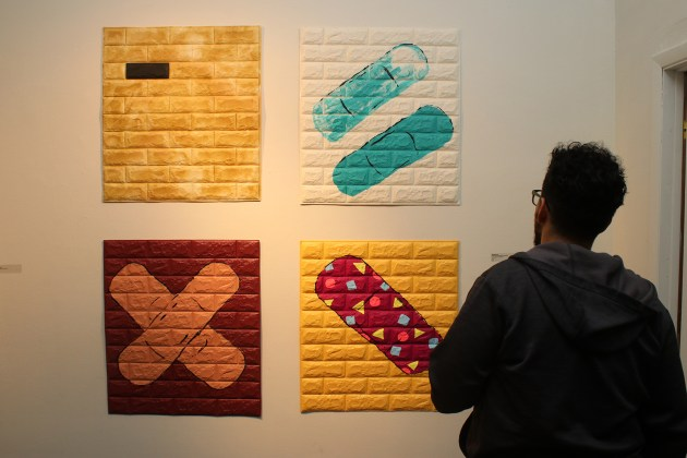 "A viewer takes in all four components of ""Philanthropic Patchwork"" during the opening reception for Martinez E-B's ""B Side"" Oct. 5 at Waterloo Arts in Cleveland."