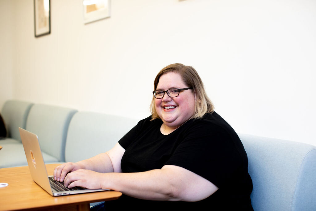 white fat woman typing on laptop, smiling at camera.