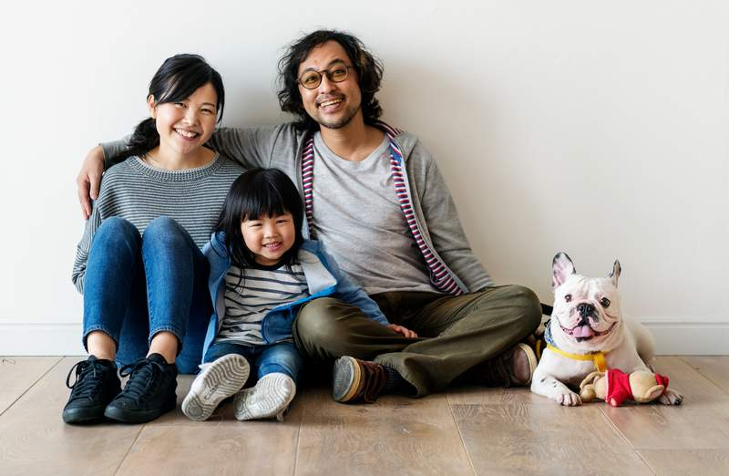 Smiling Asian family with dog - Training resources for dog owners to help them have fun with their dogs