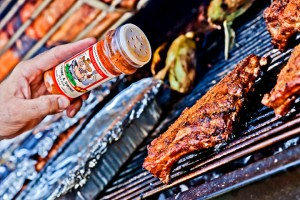 Picture of Prime and Swine dry rub being used on grilled ribs