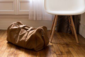 Brown duffel bag on the floor, next to a chair. To save money on packing supplies you can use duffel bags and suitcases for packing.