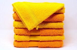 A stack of yellow and orange towels. A way to pack your bathroom with ease is to use your towels for wrapping things