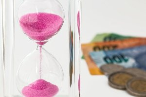 A pink hourglass with money in the background.