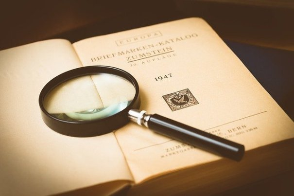 an old book and magnifying glass