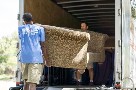 Two-Men-Moving-Couch-Into-Capital-Movers-Texas-Truck