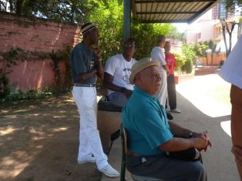 Sr. Durval do Coco observa atentamente a apresentação de capoeira.