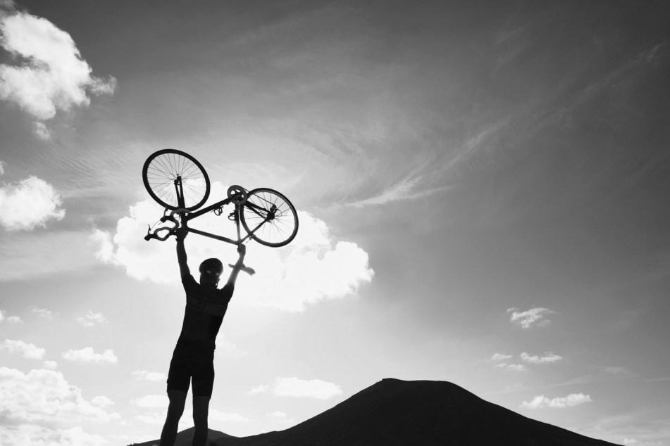 man holding bike over head