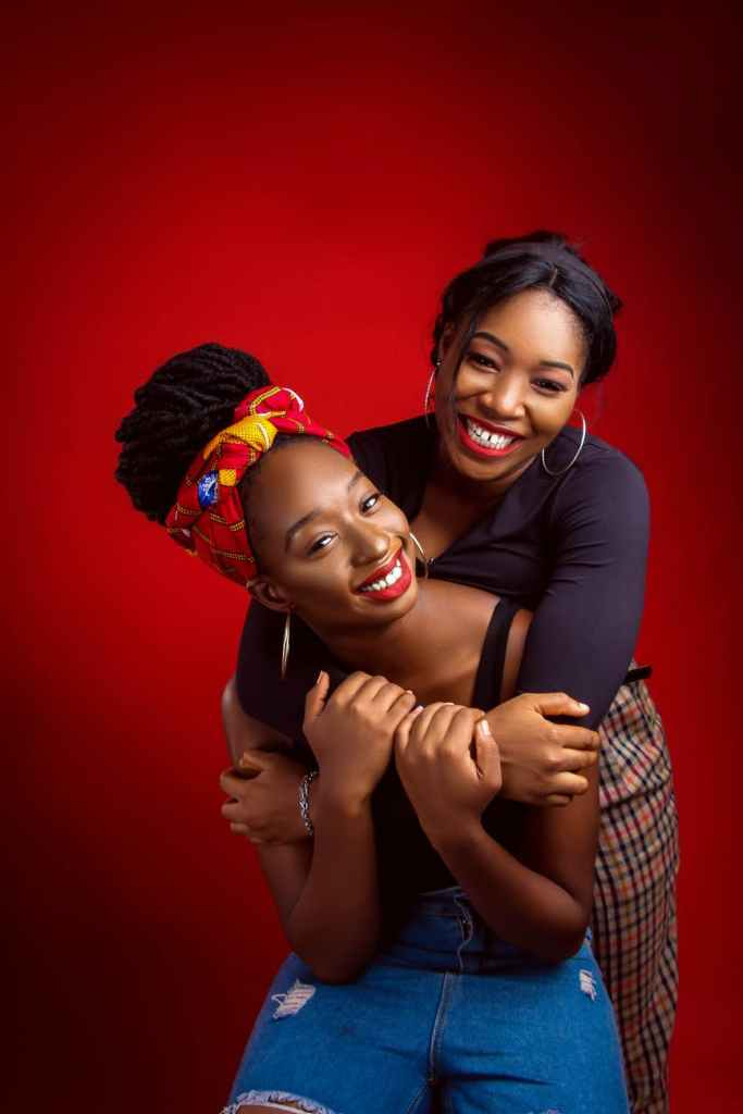 smiling black women embracing in studio