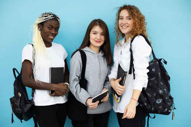 happy multiethnic female students standing together on blue background