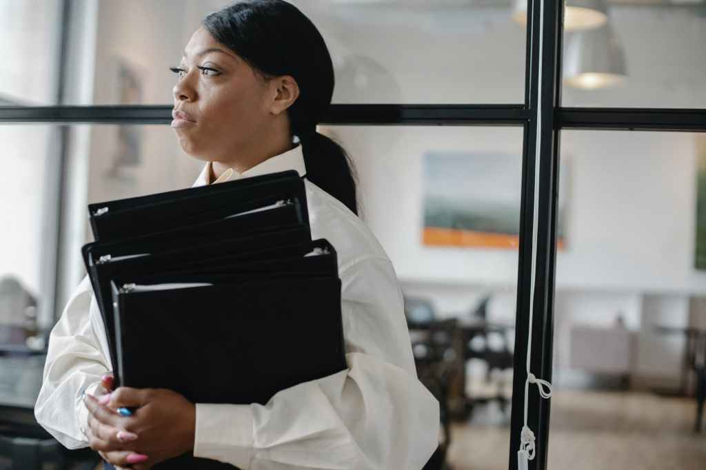 serious black woman carrying documents in office