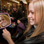 Client Admires Her New Hair Style at the Student Salon