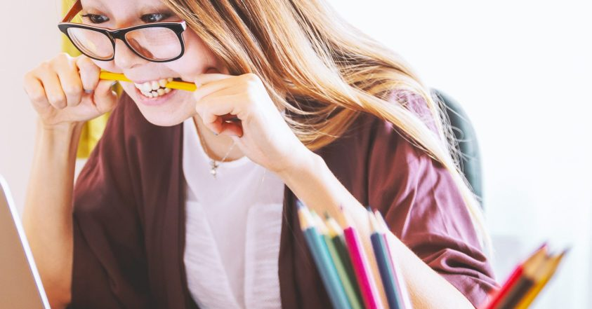 young woman on computer biting pencil