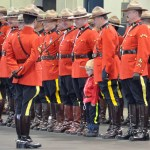 RCMP members in scarlet on parade with a young boy in RCMP costume posing with them.