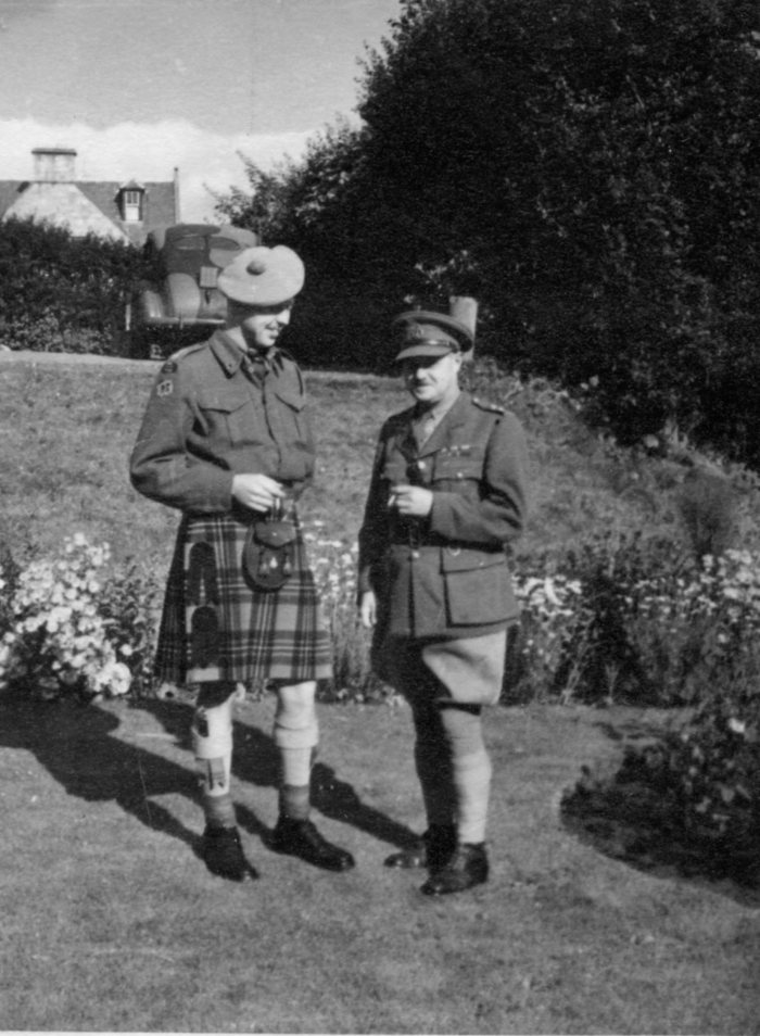 Photo of two Canadian World War II army officers in uniform standing in a scottish garden. 1943 July Lieutenant A. H. Stevens & his uncle Eric at Nairn, Invernesshire