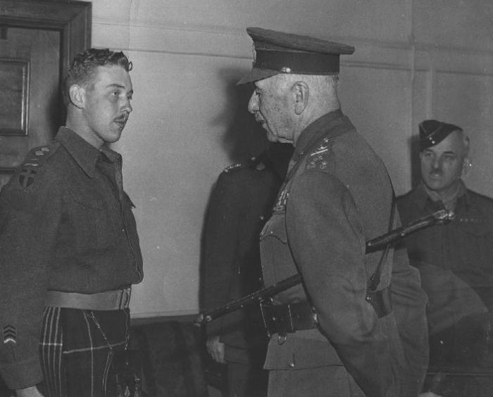 Young officer wearing a kilt on the left and old officer on right in uniform addressing him.