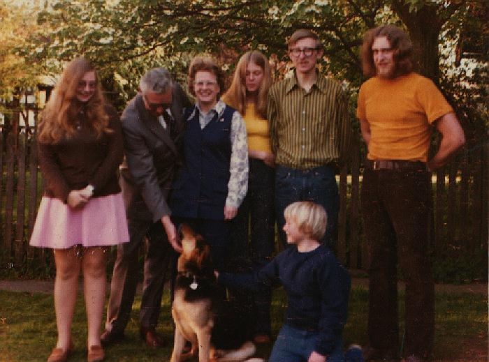 Family group of mother, father, 5 kids and dog in backyard of house in Vancouver, BC. The whole Stevens family as we were about 1973 in the backyard of our house on Osler Street in Vancouver. Rob is in front with the German Shepherd and is about 10 years old in this photo