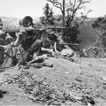 Centre is reportedly a USMC sniper M1903A4 apparently in Burma WWII. On viewer's left is an M1903A3. In front of him are rifle grenades but he does not have a grenade launcher fitted. On the far right is a Browning M1919A4 medium machine gun.