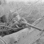 Soldier with rifle behind a large tree branch. 1942 approx Sniper in training in UK with P-14 with target sights. (L&AC MIKAN 3607526)