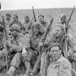 Soliders with rifles sitting on hillside on a smoke break. 1943-04-24 2 Canadian Infantry Division Sniper training England. Photo by Lieut. Dwight E. Dolan (L&AC PA-177141 MIKAN 3260082)