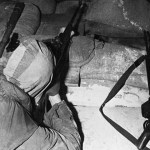 British sniper in attic aiming his rifle.