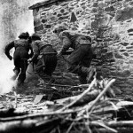 Three Brtiish soldiers rusging a stone building.