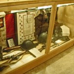 """Case 6B Seaforth Museum in 2008. Italian items. 2"""" Mortar. CANLOAN tunic of Sandy Millar who was posted to the Imperial Seaforths in WWII."""