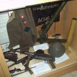 "Case 6B - Major Alex ""Sandy"" Millar's CANLOAN BD blouse and framed CANLOAN scroll; two MP-40 SMGs, Italian helmet and two versions of the 2-INCH mortar. An Italian banner captured at AGIRA is behind them."