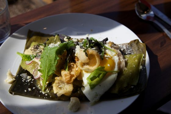 Spring Onion Tamale  Sunnyside egg, refried pinto beans, lime chicharonnes, Queso fresco, serrano chili aioli, pickled califlower