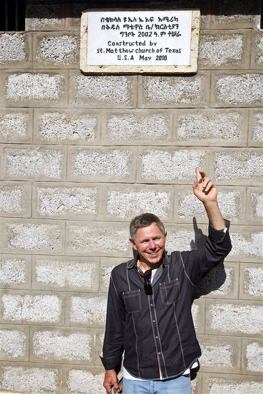 Rick standing under a plaque recognizing his church's gift of the kindergarten
