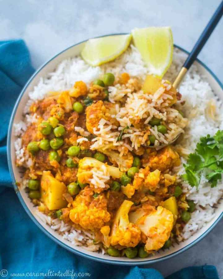 A bowl of cauliflower, peas and potatoes curry, served over rice